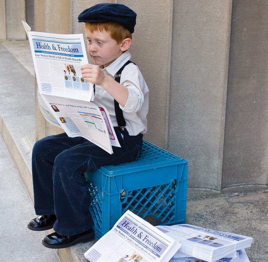 red head boy reading newspaper