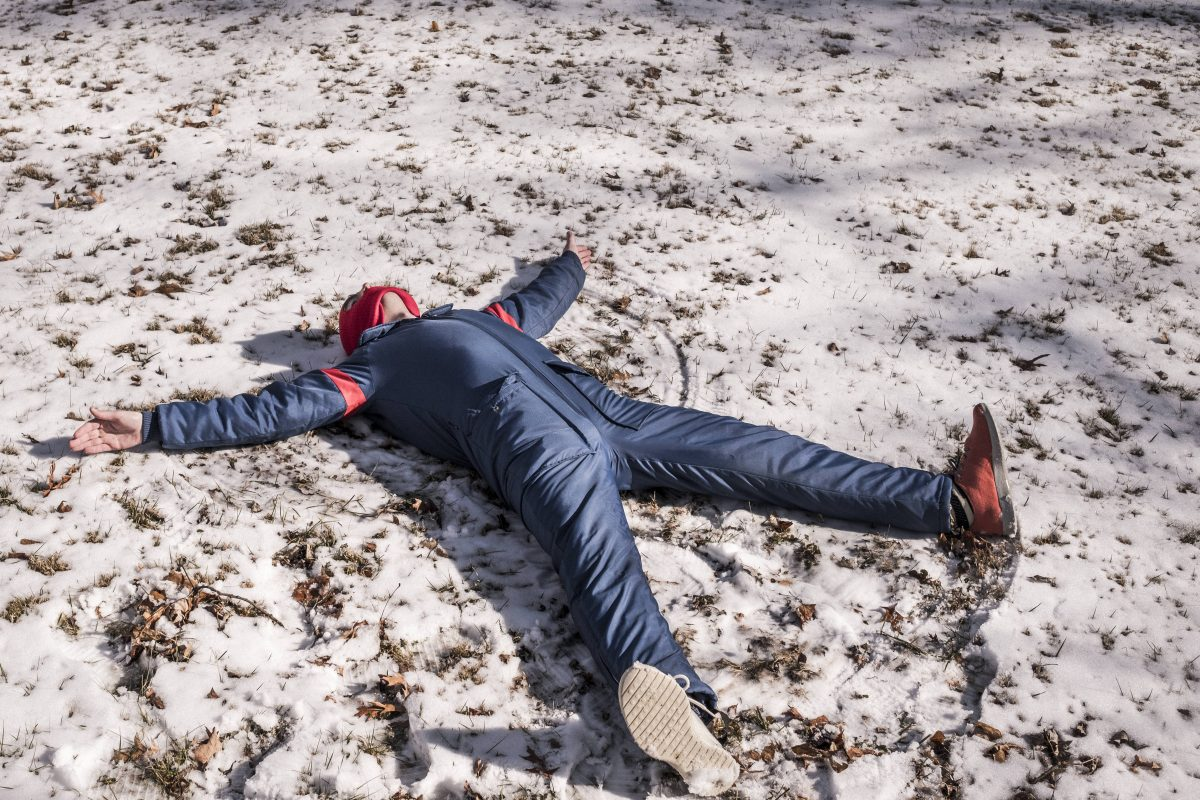 Man in snowsuit making snow angels.