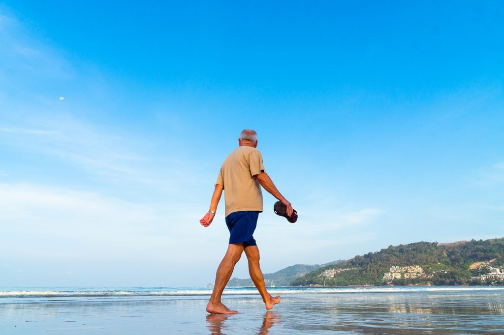 Senior man walking on beach.